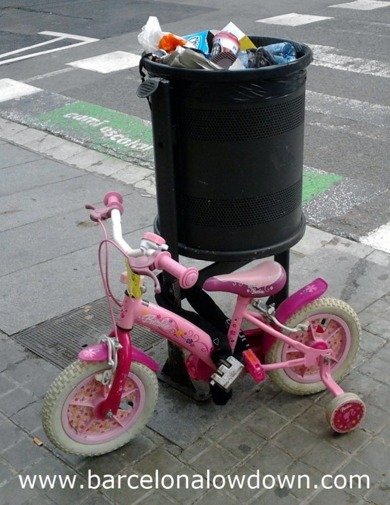 A child's bike securely chained to a litter bin in Barcelona