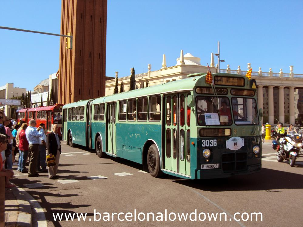 A green articulated bus in Barcelona