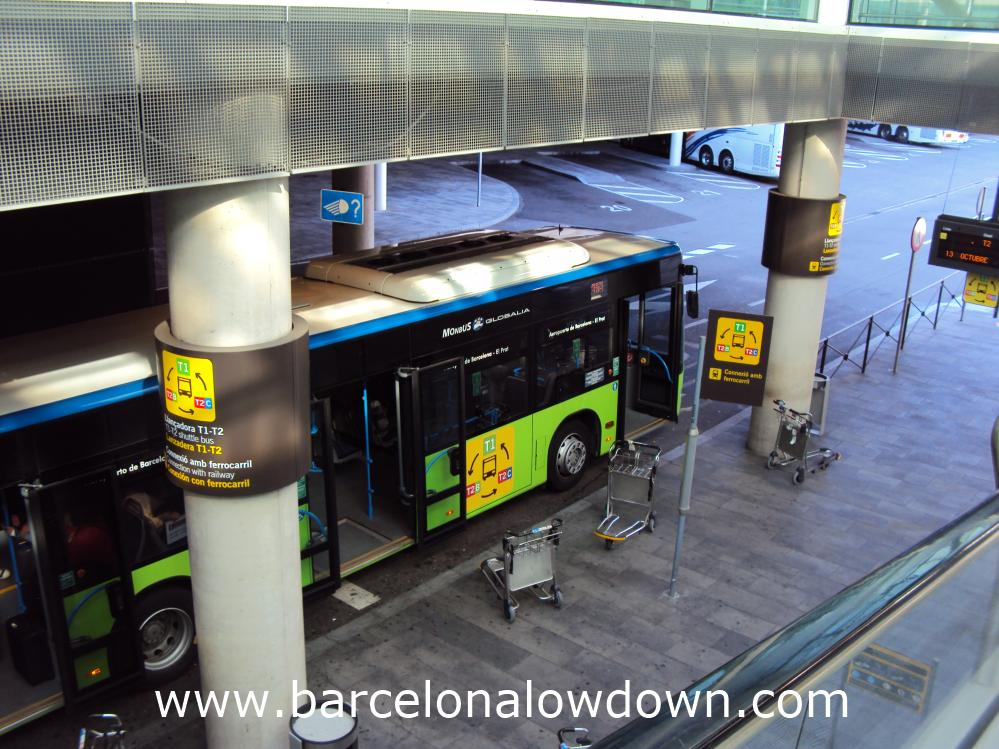The free airport shuttle bus seen from the escalator at Barcelona T1 airport