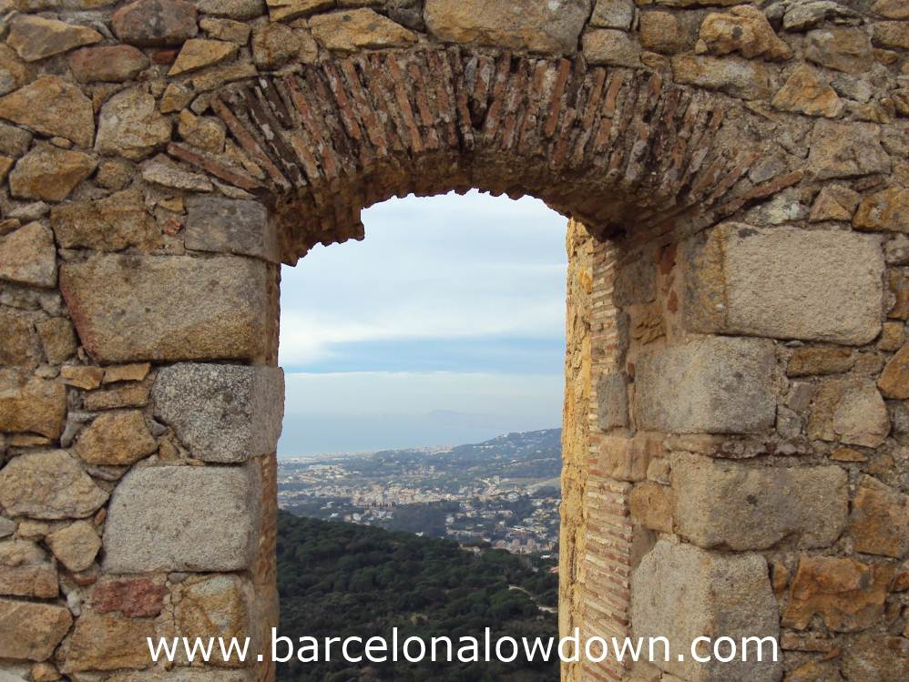 View of Barcelona through a medieval stone arch