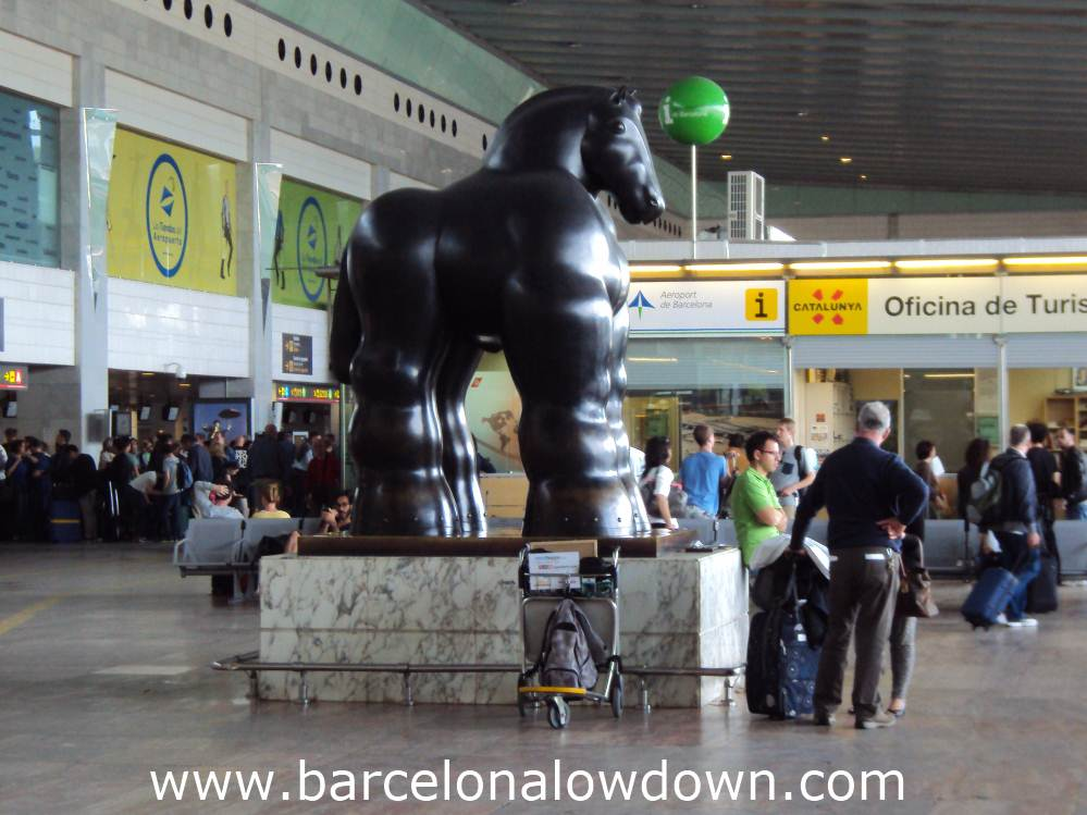 3 bored tourists waiting by Botero's black horse statue in Barcelona Airport