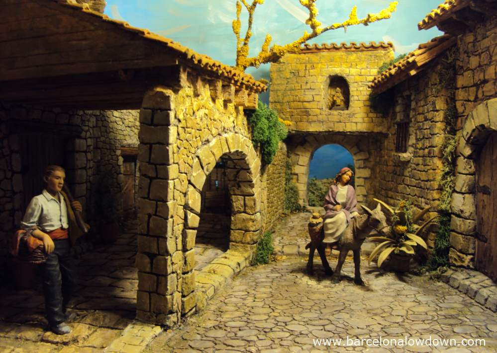 Diaorama scene depicting the virgen mary on a donkey and a peasant in traditional Catalan dress