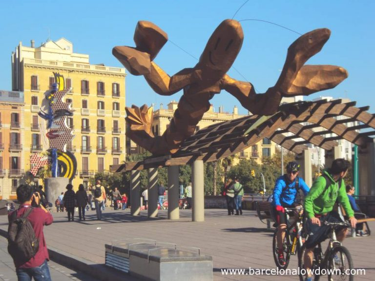 The Gambrinus giant smiling crayfish statue and the pop art style Barcelona's Head at Barcelona's Port Vell old harbour