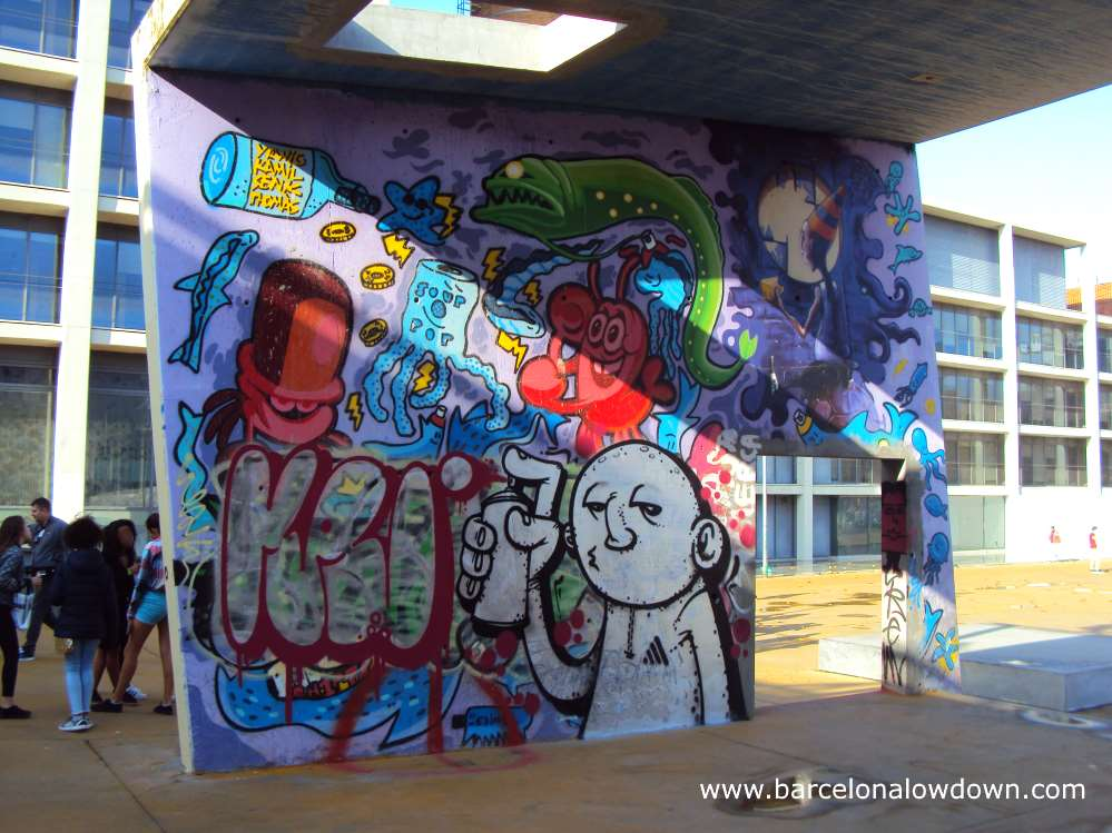 Teenagers chatting near a wall covered with graffiti in Barcelona