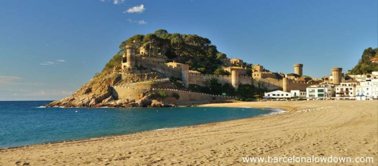 The fortified medieval town of Tossa de Mar (La Vila Vella) and the long sandy beach. A sunny day on the Costa Brava, Spain.