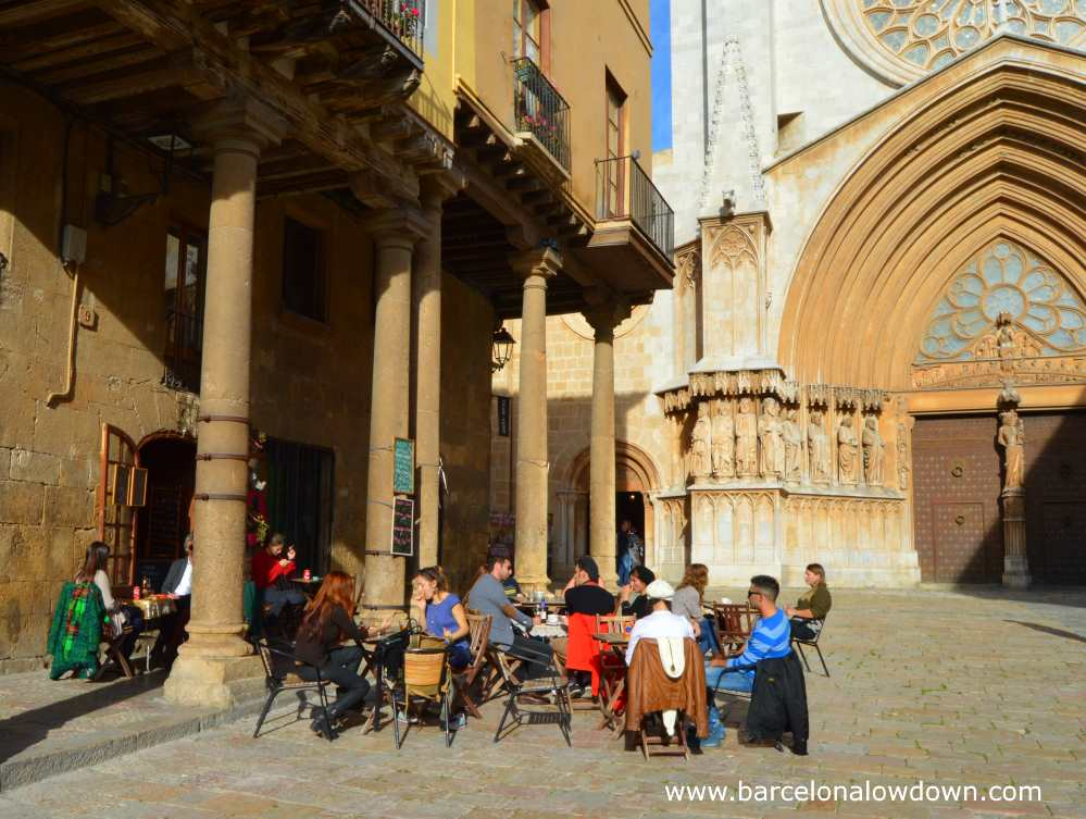 People drinking and talking on a busy terrace in front of Tarragona Cathedral