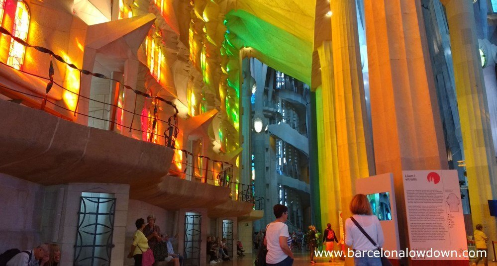 Tourists inside the Sagrada Familia, light passing through the stained glass windows on the left bathes the columns on the right hand side of the photo with a rainbow of clours