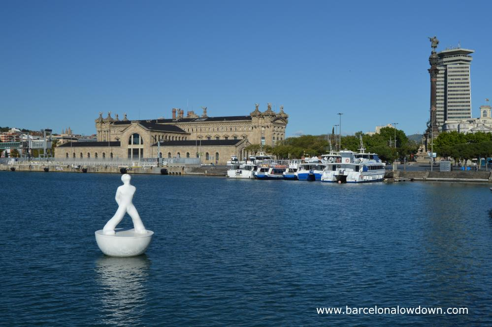 One of the white stargazer statues in front of the Columbus monument and the old harbour buildings of Barcelona's Port Vell
