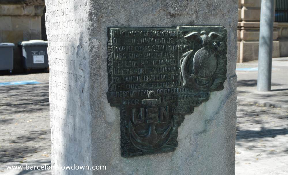 The metal plaque on the side of the monument to us servicemen in Barcelona. The design includes an eagle atop a globe and an anchor with the letters USN.