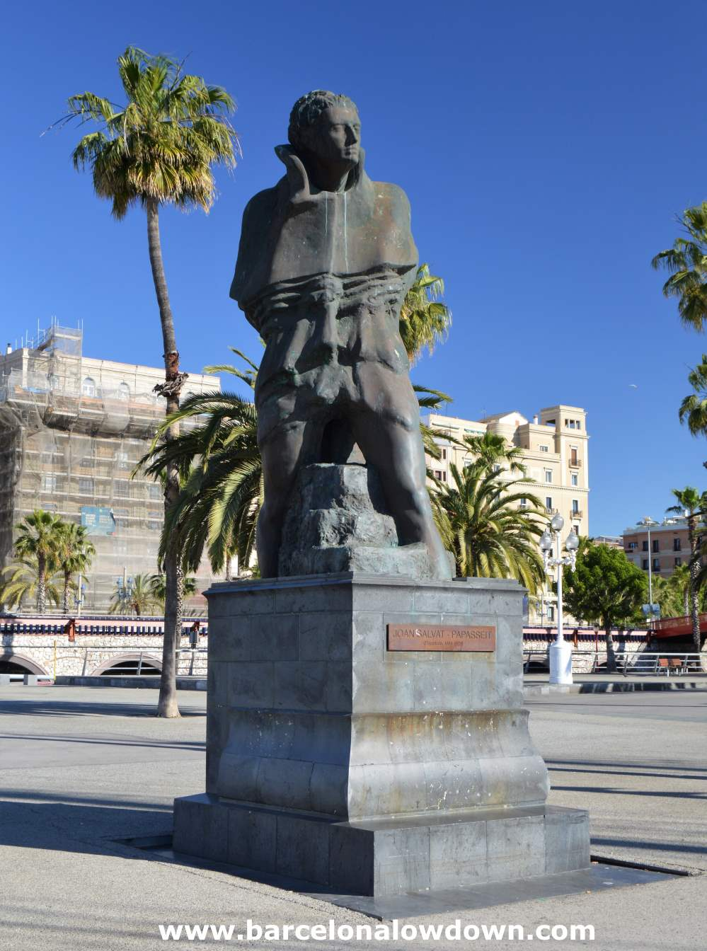 Bronze statue of the Spanish poes Joan Salvat Papasseit dressed as a night watchman overlooking the old port of Barcelona. There are several palm trees and a neo classic styled building in the background.