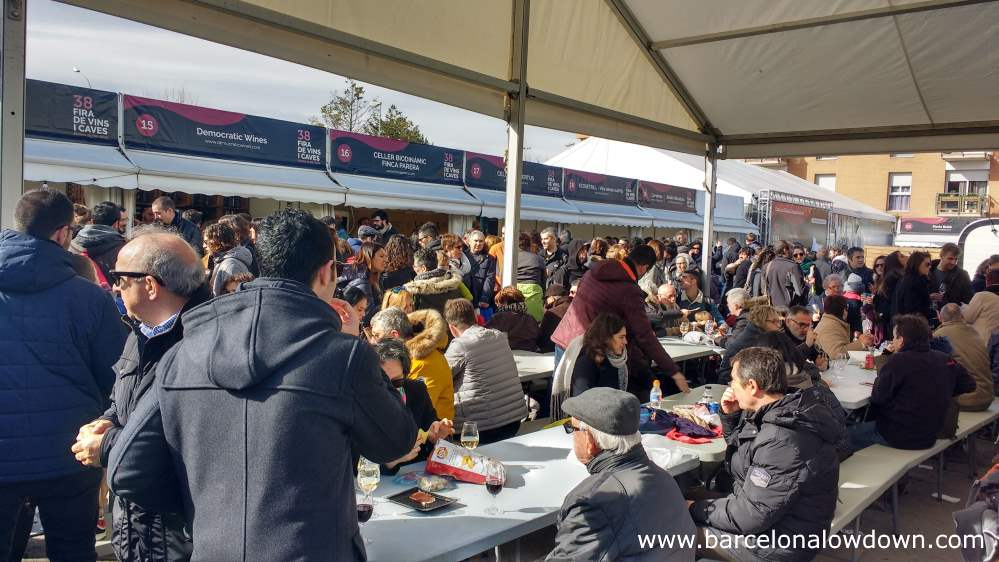 People eating and drinking wine at long tables at the anual wine festival at Molins de Rei, Barcelona, Catalonia, Spain