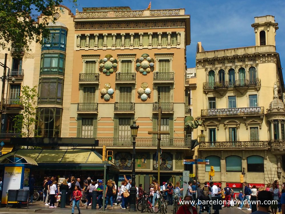 A spring day on the Ramblas, Barcelona. Crowds of tourists walking along the Ramblas boulevard, many of them are taking photos of Casa Bruna Cuadros, better known as the Umbrella House.