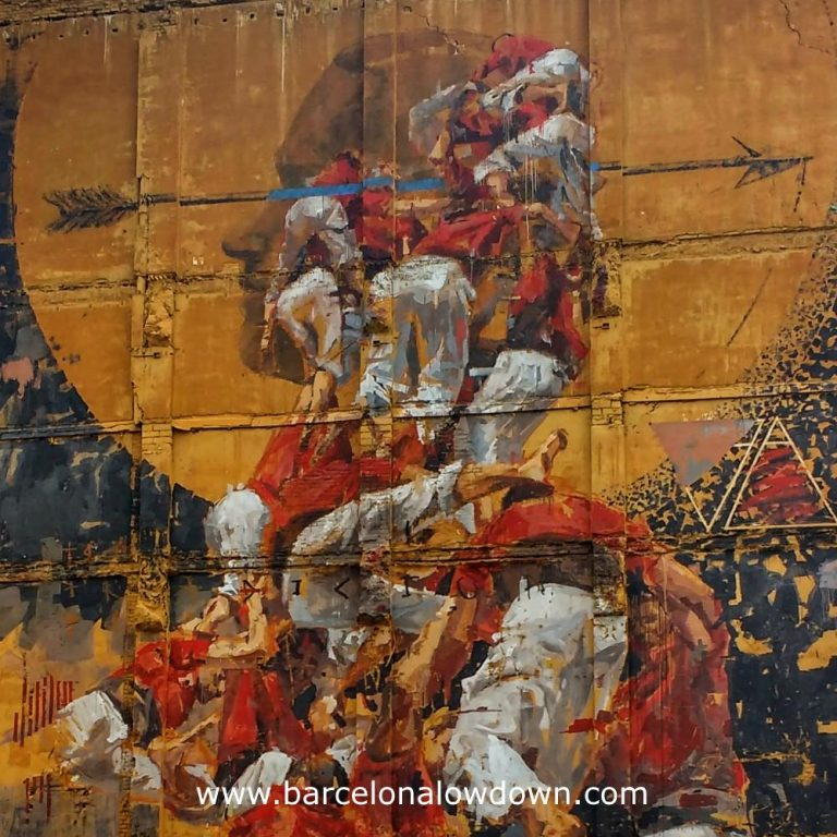 Closeup photo of the painting Fer Llenya. The painting shows a group of Castellers in the moment thet the tower collapses. The background of the painting is the siluette of a Native American whose head is traversed by an arrow.