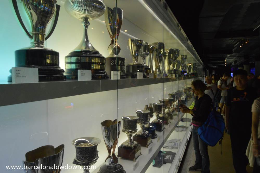 A large glass cabinet displaying football cups and trophies at the FC Barcelona museum
