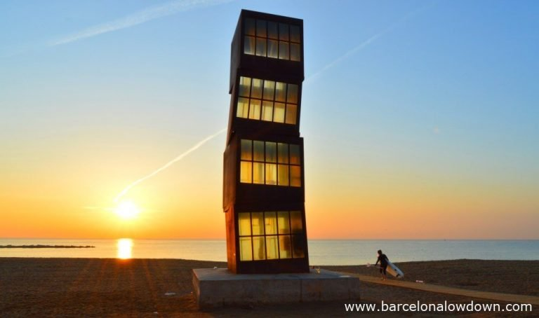 The wounded star statue at sunrise by Rebecca Horn. Photo of Barcelona beach, the early morning sunshine is shining through windows of thye rusty iron block statue staining them yellow. A lone paddlesurfer is walking across the sand carring their board towards the sea for an early morning surf session,