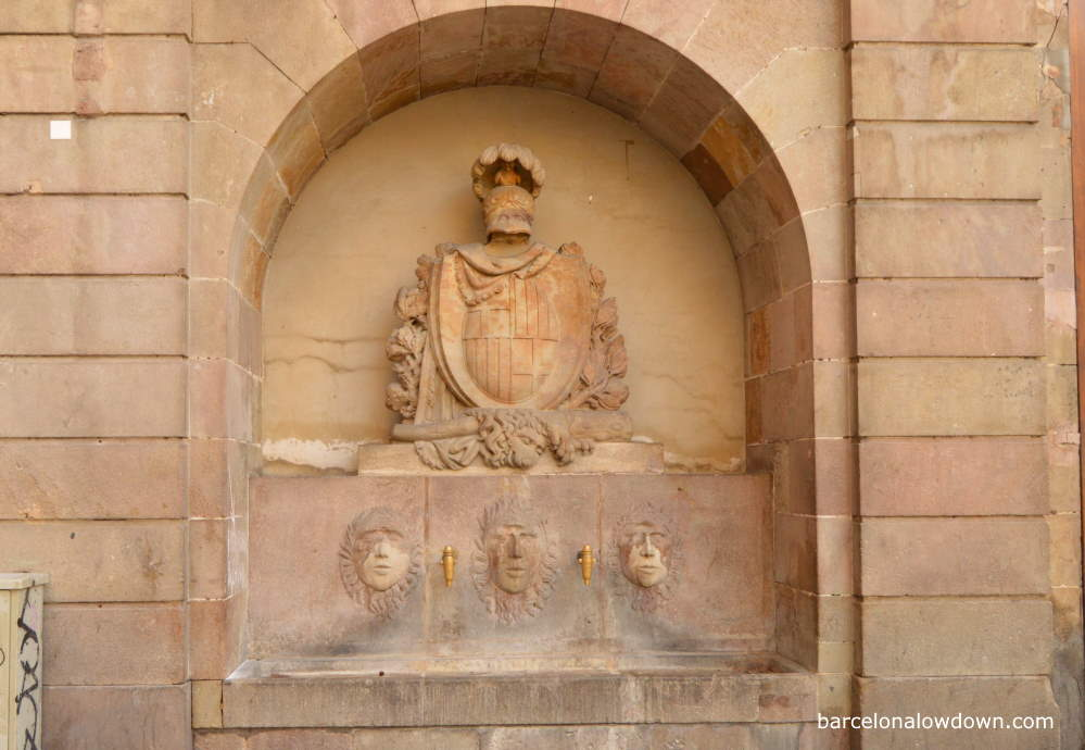 Historic fountain with brass taps and stone carvings of faces and the shield of Barcelona adorned with a helmet and lions skin