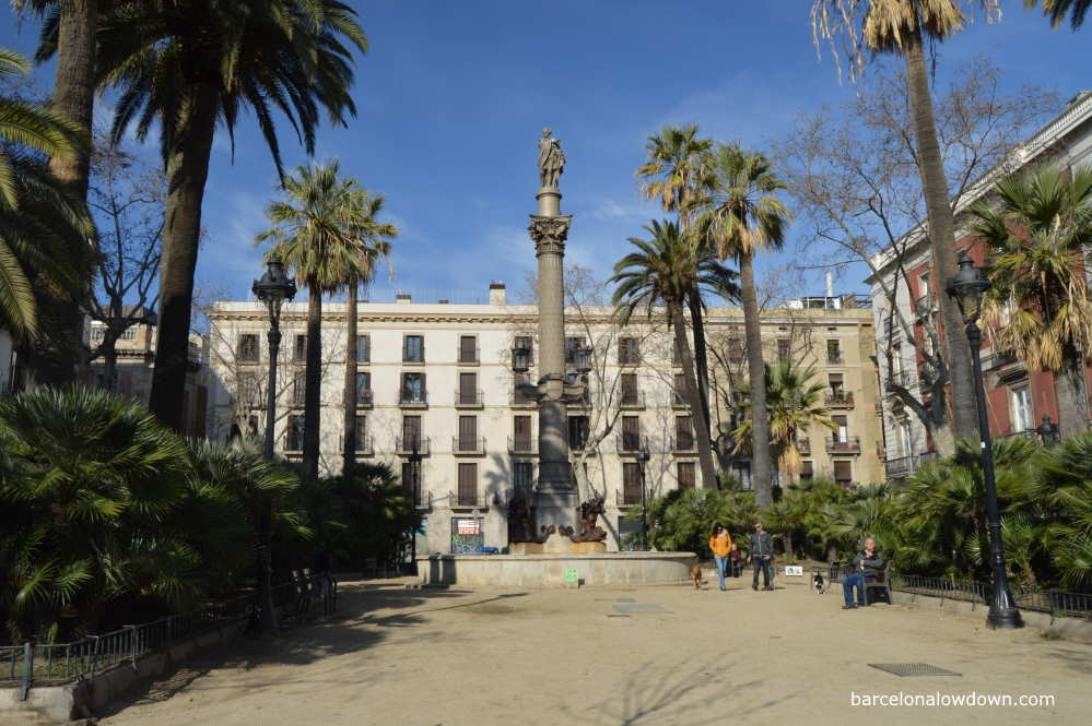 A Beautiful square with palm trees and a tall monument in Barcelona