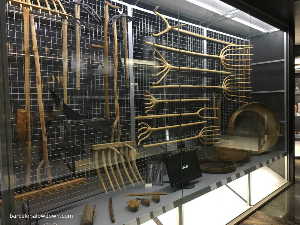 A collection of pitchforks and other farming implements on display at the Ripoll Ethnological Museum