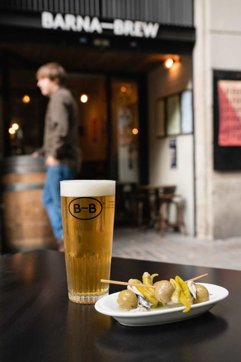 A glass of beer and some green olives on a table outside Barna Brew
