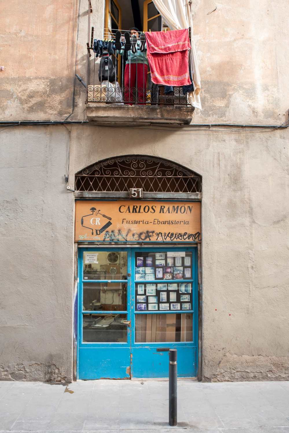 Street scene in Barcelona, a lady is hanging out washing on her balcony above a carpenter's workshop - Photo by Ben Holbrook