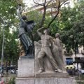 A monument in Barcelona depicting a semi nude woman holding a torch and a soviet style carving of a farmer