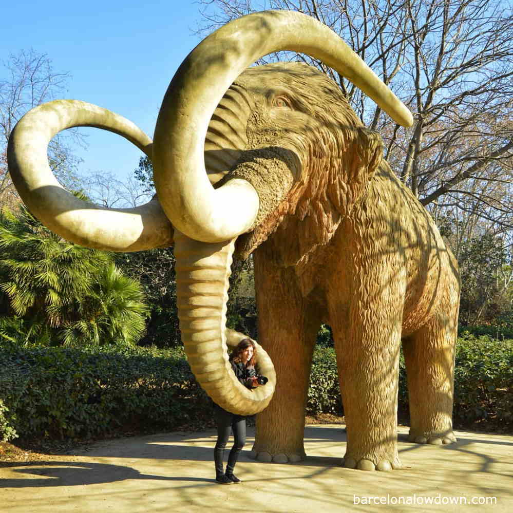 A girl posing for a photo with the woolly mammoth statue in Barcelona's Ciutadella Park