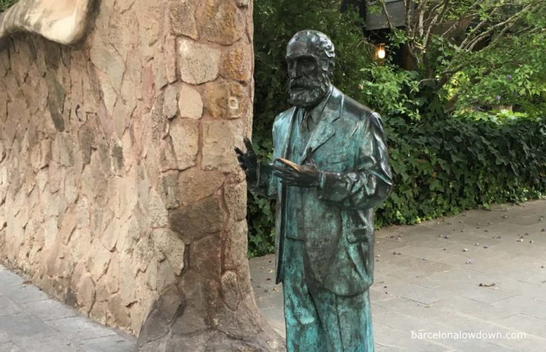 Bronze statue of Antoni Gaudí standing in front of a modernist style gateway in Barcelona