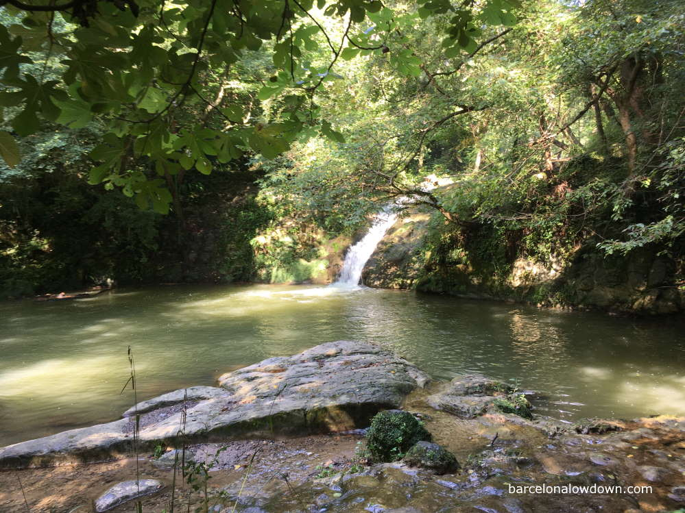 A small waterfall cascading into a swimming hole in Catalonia